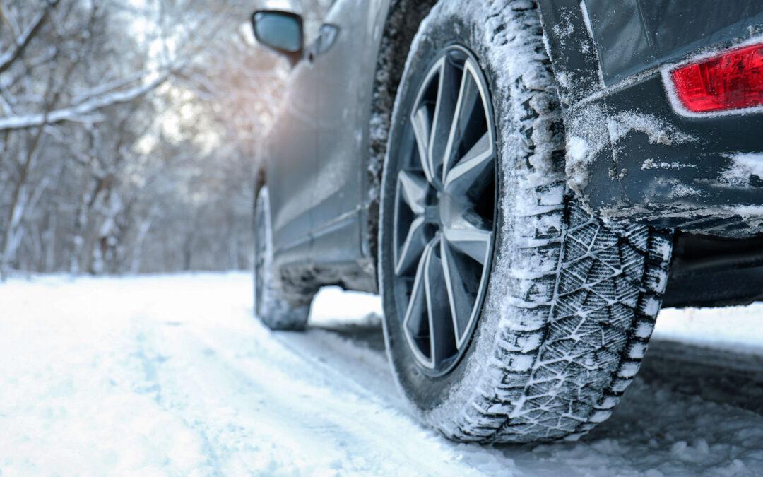 Ein Auto fährt durch ein verschneites Waldstück