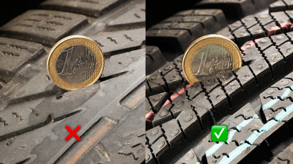 Eine 1 € Münze steckt in dem Profil eines Reifens, um die Mindestprofiltiefe zu überprüfen