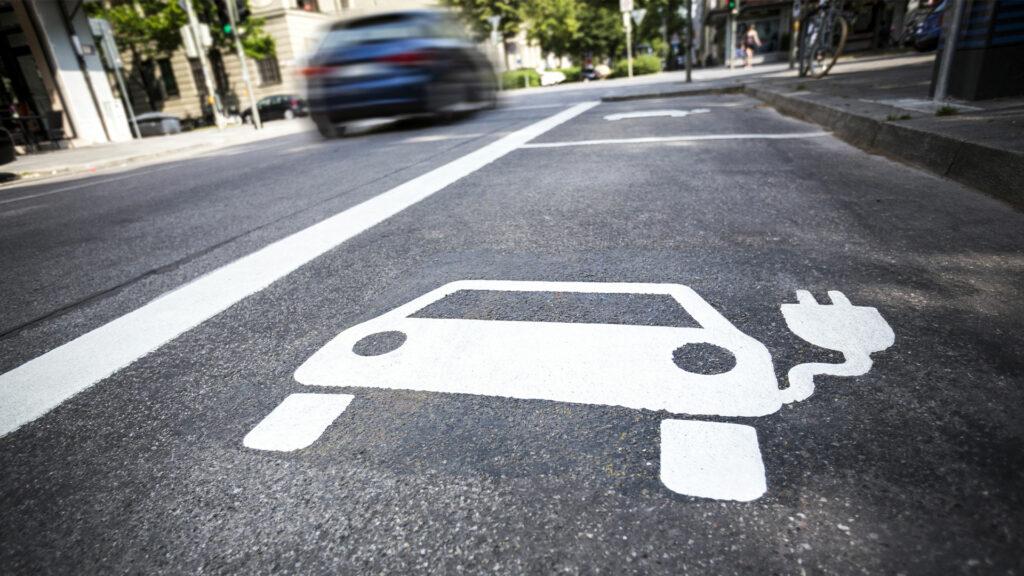 Das Symbol eines Elektroautos auf dem Asphalt eines Parkplatzes